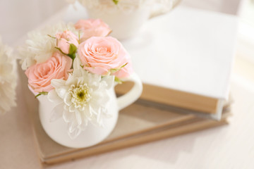 Bouquet of beautiful roses in a cup on a  book