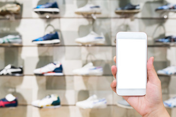 Hand hold mobile phone with sport shoes on shelves in the shoes