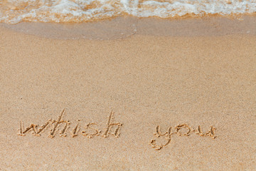 wish you - the inscription on the sand beach with a soft wave.