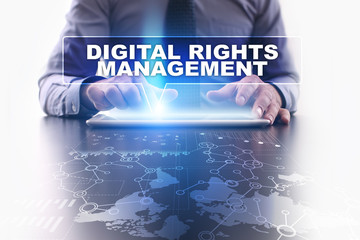 Businessman is using tablet pc, pressing on virtual screen and selecting digital rights management.