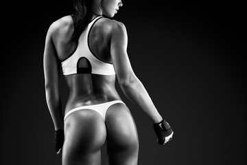 Fit young woman Muscular fitness model wearing sports bra