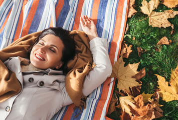Calmly smiling woman lying on the grass in autumn park
