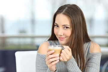 Confident woman posing holding a coffee cup