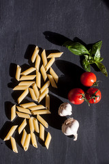 raw penne pasta with tomato, basil and garlic