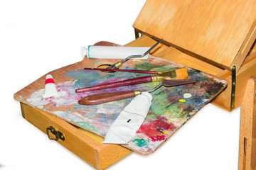 Painting tool on the palette on a wooden easel closeup