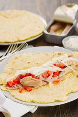 tortilla with fish salad on the plate on wooden background
