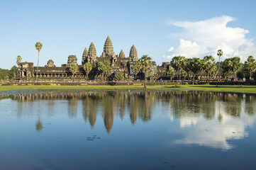 Ancient temple complex of Angkor Wat reflecting in still water under blue sky