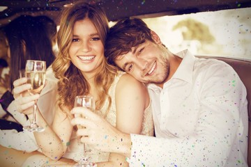 Composite image of portrait of couple holding champagne