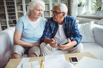 Worried senior couple interacting while checking the bills
