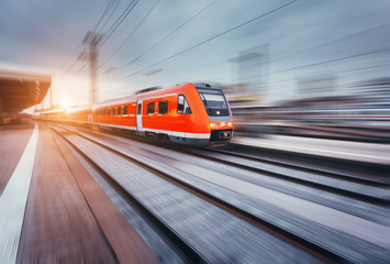 Beautiful railway station with modern high speed red commuter train with motion blur effect at colorful sunset. Railroad with sunlight. Vintage toning. Travel. Train