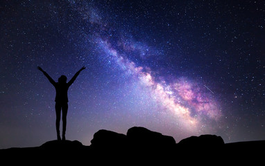 Milky Way. Night sky with stars and silhouette of a woman with raised-up arms.