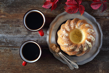 Homemade Kouglof, two cups of coffee and autumn leaves
