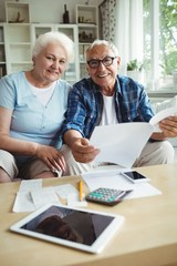 Senior couple smiling while checking the bills