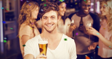 Composite image of smiling man showing beer with his friends
