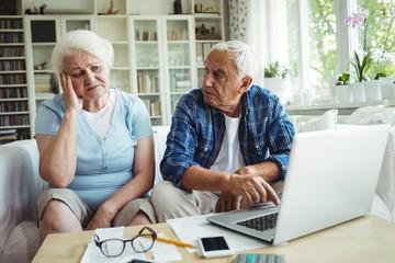 Worried senior couple using laptop