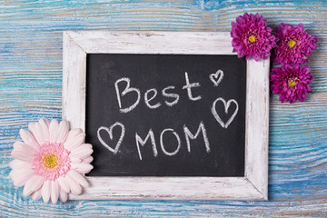 Mother's day concept, Best Mom written on chalkboard with pink flowers on wooden background