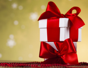 Presents with red ribbon on wooden background