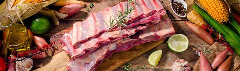Raw beef ribs and vegetables on  dark wooden background. Wall mural