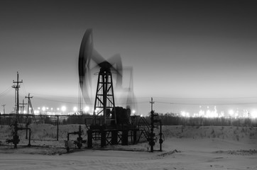 Working oil pump jack at night time. Oilfield during winter. Refinery lights background. Oil and gas concept. Black and white.