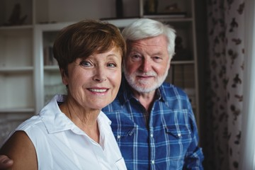 Senior couple smiling in living room