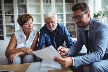Fototapeta Senior couple planning their investments with financial advisor