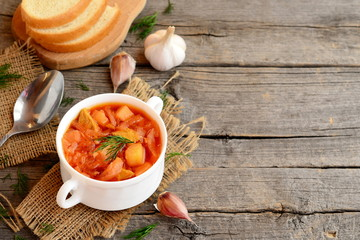 Cabbage soup with meat in a bowl, spoon, garlic, dill, pieces of bread on old wooden background with empty place for text. Soup cooked with meat, potatoes, cabbage, carrots, garlic, onion and tomato
