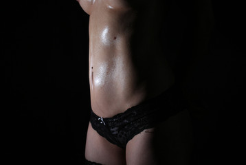 sexy woman body oiled and with water drops on black background