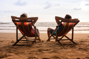Romantic couple sitting in deck chairs on sea beach at sunset