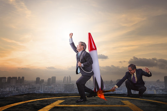 two business man playing rocket toy on high building roof with s