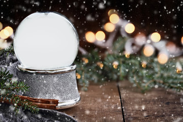 Rustic image of an empty Christmas snow globe surrounded by pine branches, cinnamon sticks and a warm gray scarf with copy space and gently falling snow. Selective focus on snowglobe.
