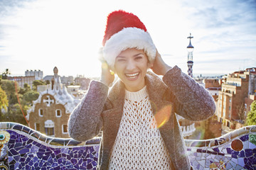 traveller woman in Santa hat at Guell Park having fun time