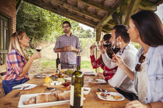 Man giving a speech at outdoor table watched by friends