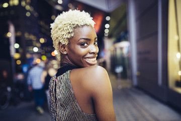 USA, New York City, smiling young woman on Times Square at night