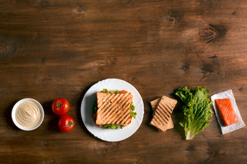 Club sandwich prepared with fish on the wooden board