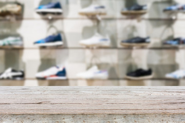 Wood table top with Shoes on shelves in the shoes store