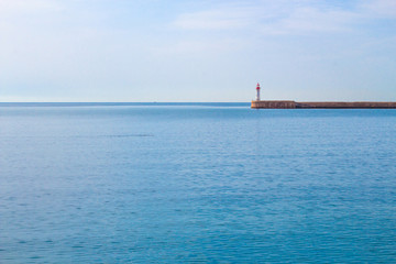 Calm sea and lighthouse at the end of the promenade.
