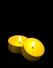 Isolated Yellow Candles on Black Background.