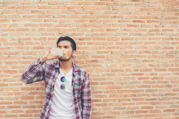 Young hipster bearded man with water bottle in plaid shirt in fr