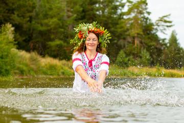 Pretty girl in national dress is in water