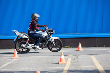 Woman L-driver doing exercise around cones on the motorbike in skill training motordrome. Russian driver school
