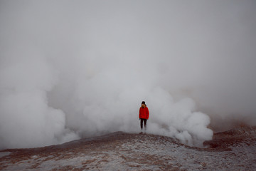 happy caucasian girl in red jacket at geyser in Bolivia
