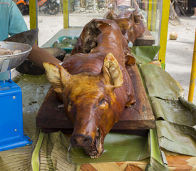 Fried whole pig on the table near a cook chief in open restaurant.