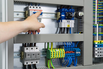 Hand eines Elektrikers zeigt auf eine Sicherung in einem Schaltschrank