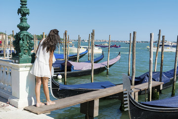 Autocollant pour porte Venise beautiful young tourist woman enjoying the venetian view with gondolas floating in the blue sea