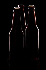 Silhouette of three brown beer bottles