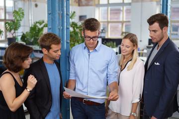junges team unterhält sich im büro und schaut auf unterlagen