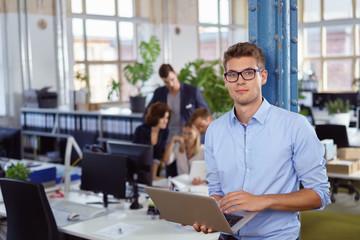 mitarbeiter steht im büro mit laptop, kollegen unterhalten sich im hintergrund