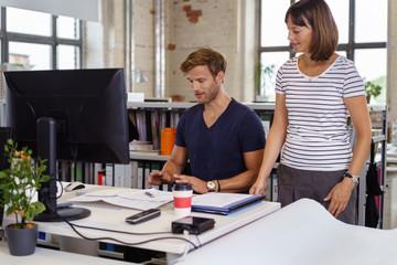 zwei kollegen im büro besprechen sich am schreibtisch