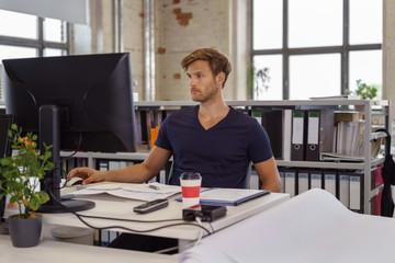 geschäftsmann sitzt schreibtisch und arbeitet konzentriert am pc
