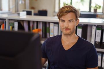 mann sitzt am schreibtisch im büro und schaut auf seinen computer